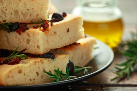 Homemade Italian focaccia with sun dried tomatoes, black olives and rosemary 스톡 콘텐츠