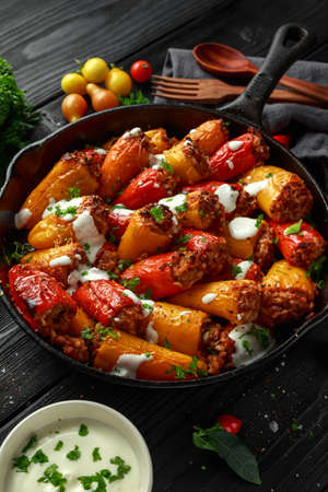 Sausage meat, mince and rice Stuffed sweet mini bell peppers baked in cast iron skillet, pan topped with yogurt and fresh parsley Imagens