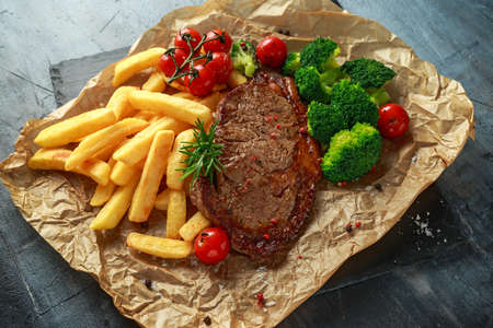 Grilled sirloin steak with potato fries, broccoli and cherry tomatoes on crumpled paper. Stock Photo