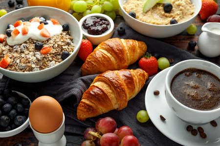 Healthy Breakfast served with coffee, orange juice, croissants, egg, cereals, oatmeal and fruits Stock Photo - 109489681