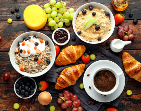 Healthy Breakfast served with coffee, orange juice, croissants, egg, cereals, oatmeal and fruits Stock Photo - 109489684