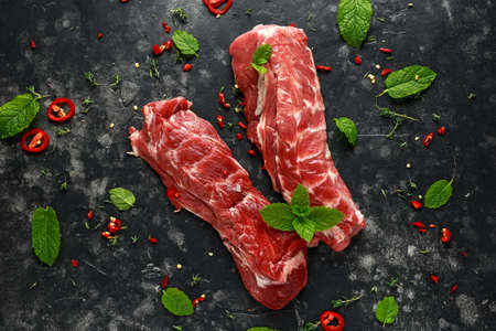Raw lamb shoulder fillets with chilli, thyme and mint leaves. Zdjęcie Seryjne - 109489698