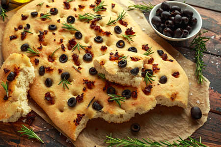 Homemade Italian focaccia with sun dried tomatoes, black olives and rosemary. Stock Photo