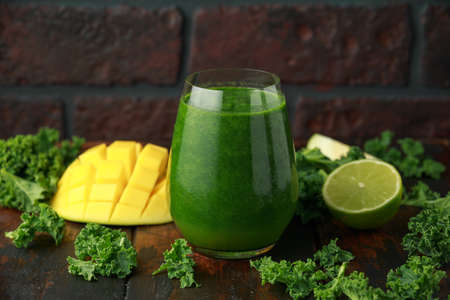 Green smoothies with kale and mango on wooden table.