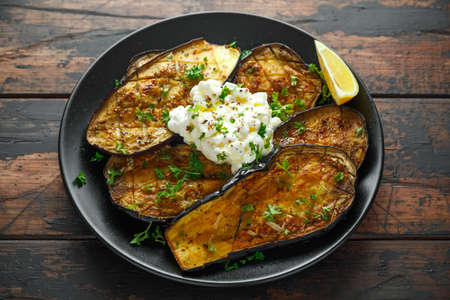 Healthy vegeterain Oven baked aubergines, Eggplant with cottage cheese dip, parsley and lemon wedge