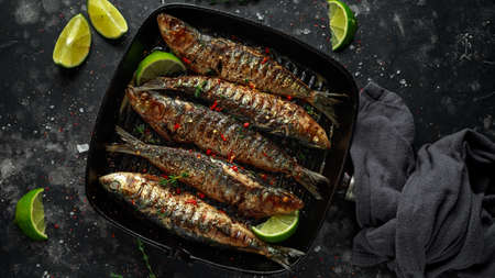 Grilled sardines with thyme, chili and lime wedges on cast iron skillet. 版權商用圖片