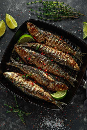 Grilled sardines with thyme, chili and lime wedges on cast iron skillet. Stock Photo