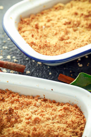 Traditional English apple crumble baked in vintage dish and served with cream.