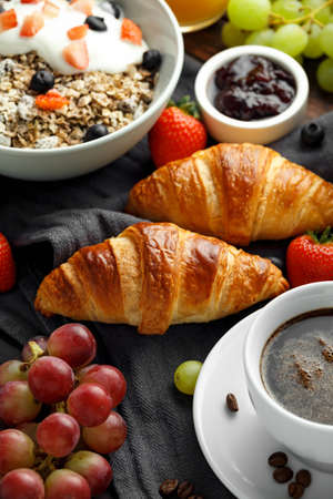 Healthy Breakfast served with coffee, orange juice, croissants, egg, cereals, oatmeal and fruits Stock Photo - 109489981