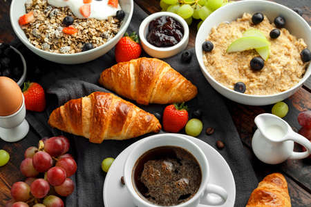 Healthy Breakfast served with coffee, orange juice, croissants, egg, cereals, oatmeal and fruits