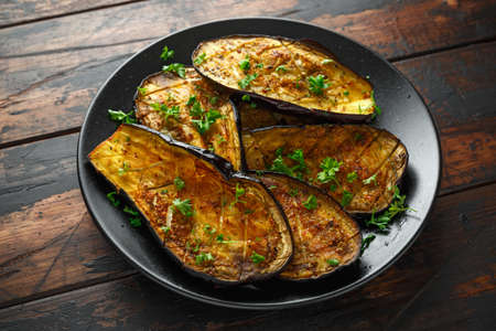 Healthy vegeterain Oven baked aubergines, Eggplant with parsley and herbs in a black plate 免版税图像