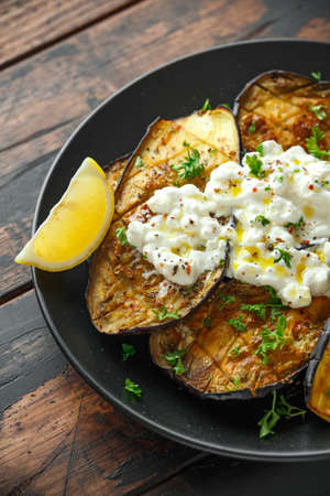 Healthy vegeterain Oven baked aubergines, Eggplant with cottage cheese dip, parsley and lemon wedge.