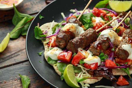 Lamb mint kebabs with flatbread, mix of vegetables, lime and greek yoghurt chilli sauce 版權商用圖片