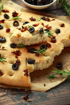 Homemade Italian focaccia with sun dried tomatoes, black olives and rosemary Stock Photo