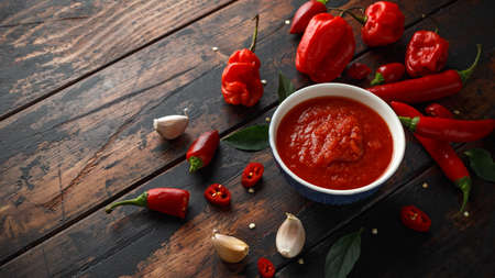 spicy hot sweet chili sauce with mix of chilli pepper, garlic and tomatoes on rustic wooden background Stockfoto