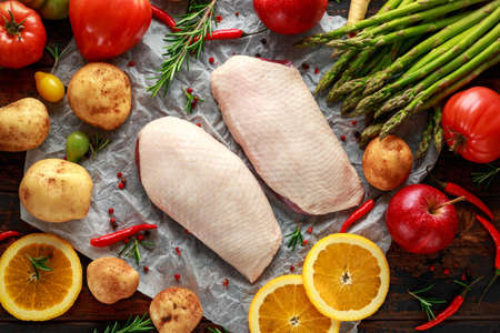 Raw Duck breast on baking paper with variety of vegetables Stock Photo