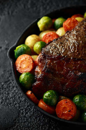 Roasted beef with honey glazed vegetables, served in cast iron vintage pan. festive dinner