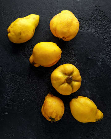 Fresh organic quince fruits on black rustic background.