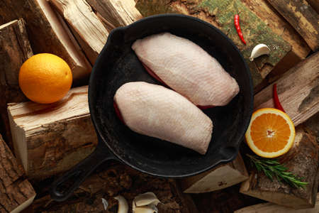 Raw duck brest fillets in rustic cast iron pan, skillet on firewood Stock Photo