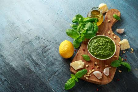 Green Basil Pesto with parmesan cheese, pine nuts, garlic and lemon on wooden board Zdjęcie Seryjne