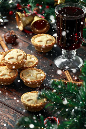 British Christmas mince pies with decoration, gifts, snow, green tree branch on wooden rustic table Stock Photo