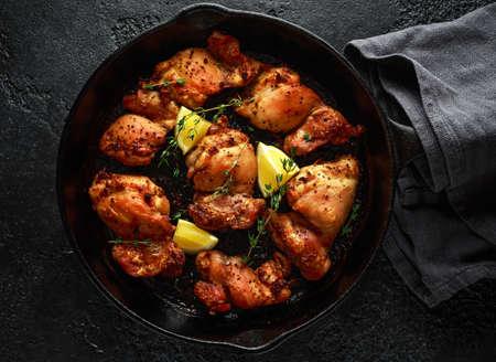 Muslos de pollo asados, deshuesados y sin piel con aderezo de tomillo y limón, servidos en una sartén de hierro fundido vintage