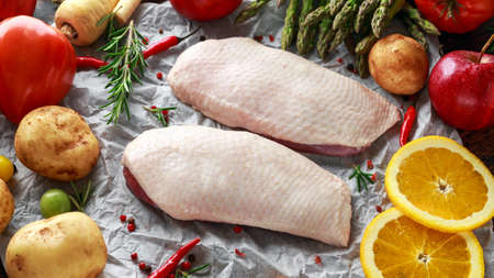 Raw Duck breast on baking paper with variety of vegetables Imagens