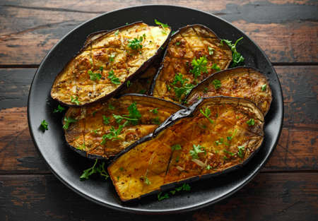 Healthy vegeterain Oven baked aubergines, Eggplant with parsley and herbs in a black plate Foto de archivo