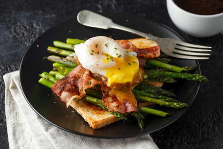 egguf de canard poché Benedict avec bacon croustillant et asperges frites sur toasts pour le petit déjeuner