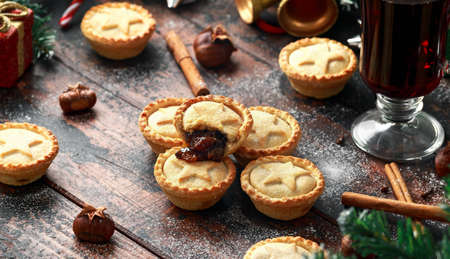 British Christmas mince pies with decoration, gifts, green tree branch on wooden rustic table Stock Photo - 113326255