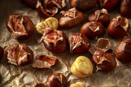 Roasted shell chestnuts served on crumpled paper