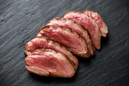 Medium rare venison steak on rustic dark stone board Stock Photo