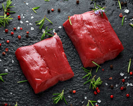 Raw venison steak with rosemary and pepper on black rustic table. Stock Photo - 113326497
