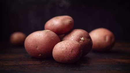 Raw red potato on windows magic light. rustic style