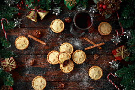 British Christmas mince pies with decoration, gifts, green tree branch on wooden rustic table Stock Photo - 113326712