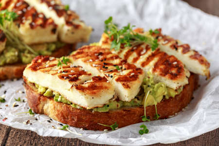 Avocado and grilled haloumi cheese toast with nigella and sesame seeds on crumpled paper. healthy breakfast 免版税图像 - 113326720