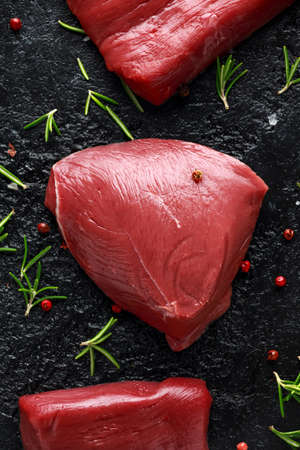 Raw venison steak with rosemary and pepper on black rustic table. Stock Photo
