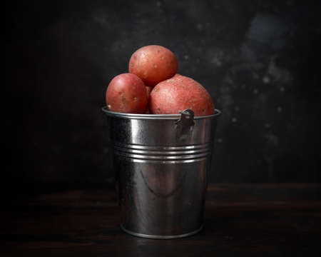 Raw red potato in metal bucket on windows light. rustic style