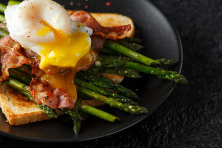 Benedict poached Duck egg with crispy bacon and fried asparagus on toasts for breakfast