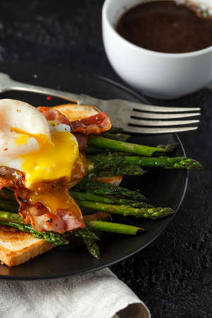 Benedict poached Duck egg with crispy bacon and fried asparagus on toasts for breakfast Archivio Fotografico - 113327032
