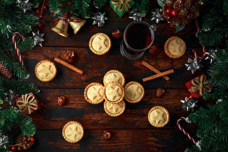 British Christmas mince pies with decoration, gifts, green tree branch on wooden rustic table Stock Photo