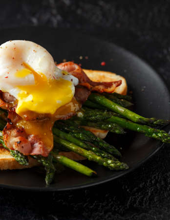 Benedict poached Duck egg with crispy bacon and fried asparagus on toasts for breakfast Archivio Fotografico - 113327133
