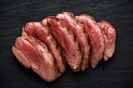 Medium rare venison steak on rustic dark stone board Stock Photo