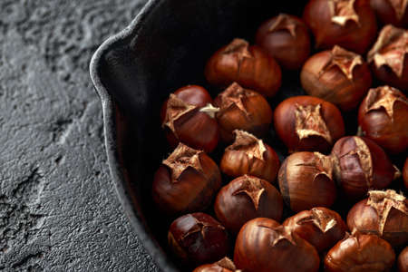 Roasted chestnuts served in cast iron vintage pan.