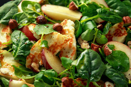 Grilled Halloumi Cheese salad with peach fruit, nuts and spinach, arugula mix. healthy food. closeup Фото со стока