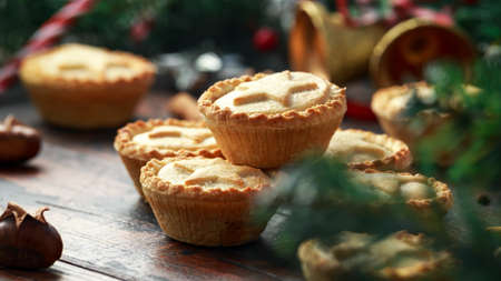British Christmas mince pies with decoration, gifts, green tree branch on wooden rustic table