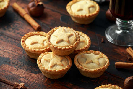 British Christmas mince pies with decoration, gifts, green tree branch on wooden rustic table Stock Photo - 113327191