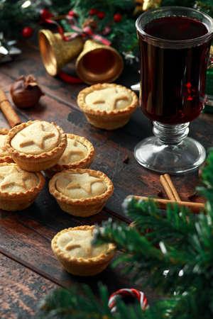 Britische Weihnachts-Mince Pies mit Dekoration, Geschenken, grünem Ast auf rustikalem Holztisch Standard-Bild