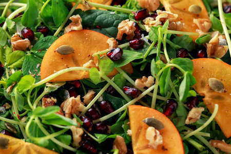 Tasty Persimmon and pea shoot salad with walnuts, pomegranate and pumpkin seed in a white plate