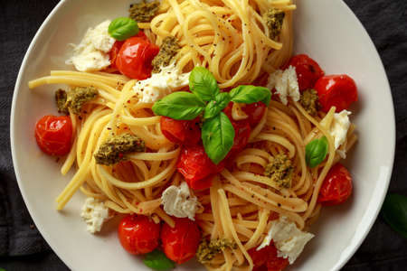 Pasta with green pesto sauce, roasted cherry tomatoes and mozzarella cheese in white plate on dark rustic background Stock Photo